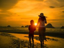 Silhouette de main et de promenade d'enfant de participation de mère sur la plage pendant le coucher du soleil Photos libres de droits