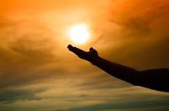 Silhouette de main sous le coucher du soleil Photos libres de droits