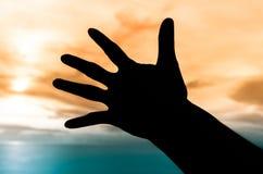 Silhouette de main sous le coucher du soleil Images stock
