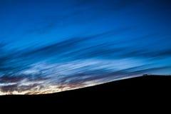 Silhouette de montagne de fin de soirée avec la barrière et la porte sur la crête Image libre de droits