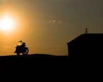 Silhouette de moto contre le coucher du soleil Images libres de droits