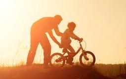 Silhouette de père enseignant sa fille à monter un vélo au coucher du soleil photos libres de droits