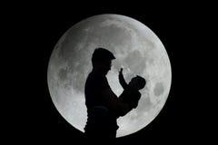 Silhouette de père et d'enfant avec la lune Images stock