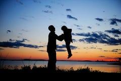 Silhouette de père et de descendant dans le coucher du soleil Photo stock