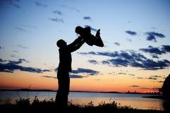 Silhouette de père et de descendant dans le coucher du soleil Images stock