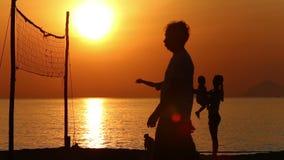 silhouette de père fonctionnant à la famille sur la plage au lever de soleil banque de vidéos