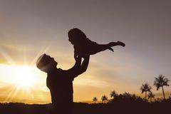Silhouette de père heureux et petite de fille jouant ensemble Images stock