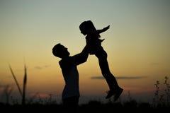 Silhouette de père jetant sa fille heureuse dans le ciel au coucher du soleil photographie stock