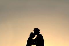 Silhouette de père Kissing Young Child sur le front image stock