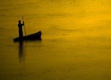 Silhouette de pêcheur au coucher du soleil Photographie stock libre de droits