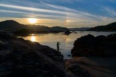 Silhouette de pêcheur au coucher du soleil Photo stock