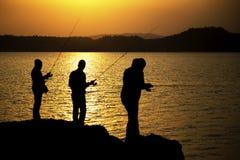 Silhouette de pêcheur avec le coucher du soleil Photos libres de droits