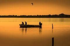 Silhouette de pêcheur avec le coucher du soleil Image libre de droits