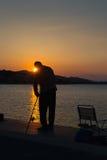 Silhouette de pêcheur contre le coucher du soleil Image stock