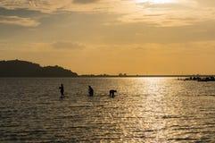 Silhouette de pêcheur dans le coucher du soleil Photos stock
