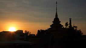 Silhouette de pagoda et de ville contre le coucher du soleil Photos stock