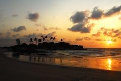 Silhouette de palmier à la plage pendant le coucher du soleil orange et les nuages dans le ciel Photo libre de droits