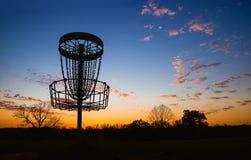 Silhouette de panier de golf de disque contre le coucher du soleil Images stock