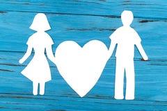 Silhouette de papier de l'homme et de la femme tenant le coeur Photo stock