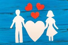 Silhouette de papier de l'homme et de la femme tenant le coeur Image stock