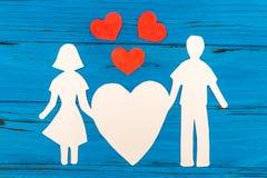 Silhouette de papier de l'homme et de la femme tenant le coeur Images stock