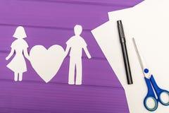 Silhouette de papier de l'homme et de la femme tenant le coeur Photos stock
