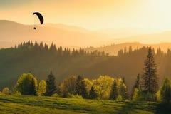 Silhouette de parapentiste au-dessus de la vallée de montagne au coucher du soleil Photos stock