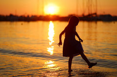 Silhouette de petites filles par la baie de mer sur le coucher du soleil Image stock