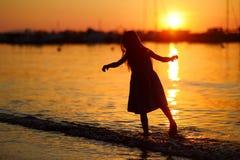 Silhouette de petites filles par la baie de mer sur le coucher du soleil Images stock