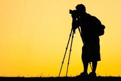 Silhouette de photo de tir de photographe pour un lever de soleil Image libre de droits
