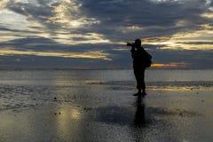 Silhouette de photographe à la plage pendant le coucher du soleil étonnant Images stock