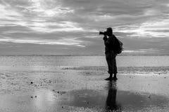 Silhouette de photographe à la plage pendant le coucher du soleil paradis de nature d'élément de conception de composition Images stock