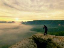 Silhouette de photographe au-dessus d'une mer de nuages, montagnes brumeuses Image libre de droits