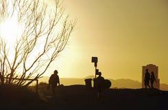 Silhouette de piste de marche de plage de gens différents Photos stock