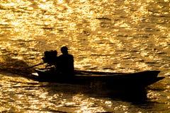 Silhouette de plan rapproché de bateau de pêcheur en rivière sur le soleil d'or Images libres de droits