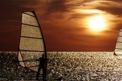 Silhouette de planche à voile sur un fond de coucher du soleil Photos libres de droits