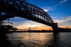 Silhouette de pont de pont et de Triborough en porte d'enfer au-dessus de la rivière avant coucher du soleil Images libres de droits