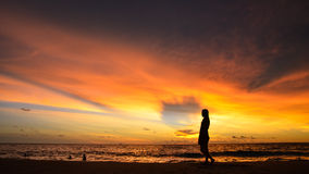 Silhouette de portrait de jeune femme par la mer quand coucher du soleil Image stock
