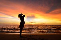 Silhouette de portrait de jeune femme par la mer quand coucher du soleil Photos libres de droits
