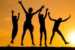 Silhouette de quatre enfants sautants contre le coucher du soleil Images stock
