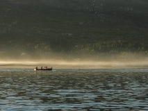 Silhouette de quatre hommes dans le canoë avec des palettes au backgroun de forêt image libre de droits