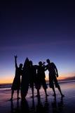 Silhouette de quatre hommes retenant une planche de surfing sur la plage Image libre de droits