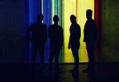 Silhouette de quatre personnes se tenant sur le fond accentué de mur Photographie stock libre de droits
