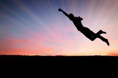 Sauter de l'adolescence dans le coucher du soleil pour l'amusement photographie stock libre de droits