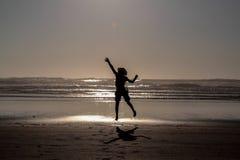 Silhouette de sauter de fille haut sur une plage images libres de droits