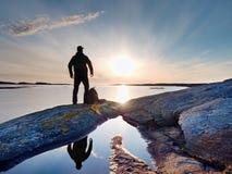 Silhouette de seul homme regardant vers le coucher du soleil vibrant Fusée et reflété en eaux peu profondes photos libres de droits