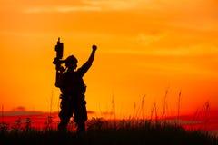 Silhouette de soldat ou de dirigeant militaire avec des armes au coucher du soleil illustration stock