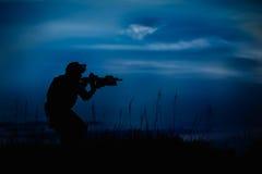 Silhouette de soldat ou de dirigeant militaire avec des armes la nuit illustration stock