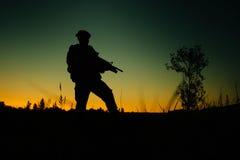 Silhouette de soldat ou de dirigeant militaire avec des armes la nuit image stock