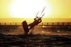 Silhouette de sportif de Kiteboarding, coucher du soleil en mer Photos libres de droits